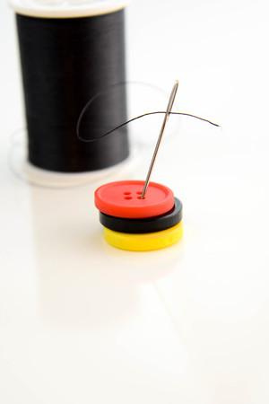 carrete negro de hilo, aguja y botones rojos, negros y amarillos