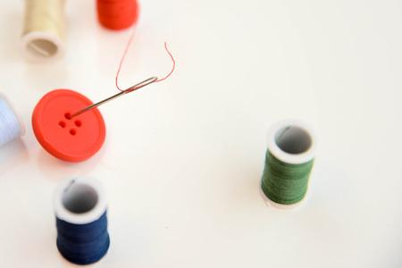 hilo rojo a través del ojo de la aguja y botón rojo con carretes de hilo de varios colores