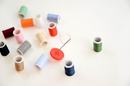 針の目とマルチで赤いボタンを赤い糸色の糸のスプール