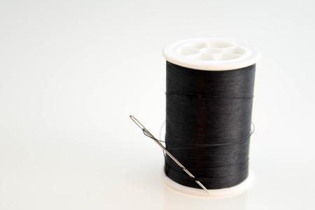 黒のスプールの糸と針のスレッドで立ち往生