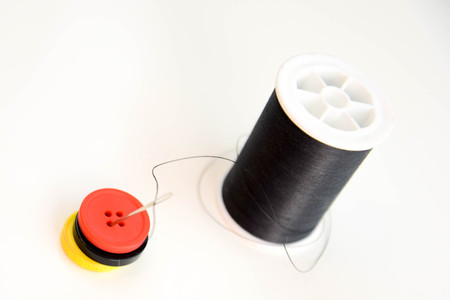 black spool of thread, needle and red, black and yellow buttons Stockfoto