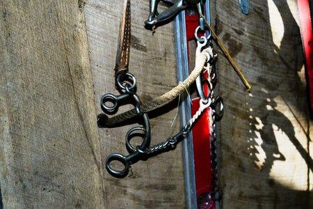 equipo ecuestre desgastado que cuelga en un granero
