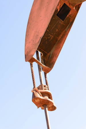old rusty oil derrick in sunlight with blue sky
