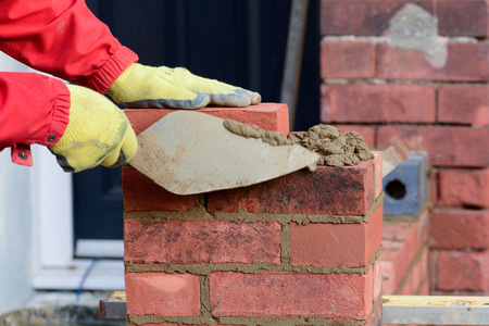Bricklaying - tidying render with trowel Stock Photo