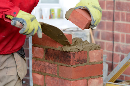 brick work: Bricklaying - about to lay a brick Stock Photo