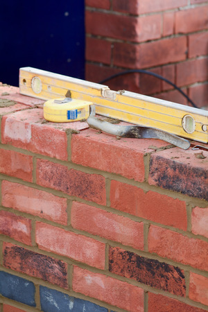 Bricklaying tools on top of wall