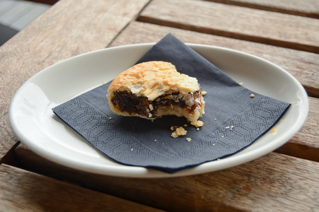 Half eaten eccles cake on plate Stock Photo