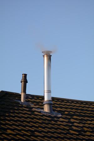 emerging: Smoke emerging from aluminum chimney Stock Photo