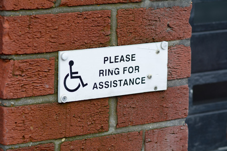 wheelchair users: Please Ring for Assistance sign for wheelchair users Stock Photo