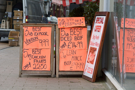 garish: Signs outside butchers shop with offers Stock Photo