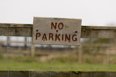 no  parking: No Parking sign on wooden fence Stock Photo