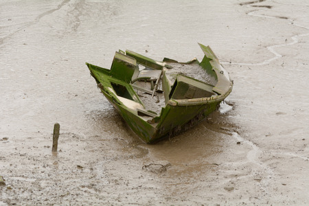 holed: Rotten and broken hull of small boat in river