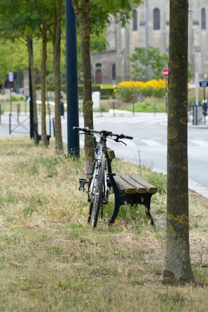 padlocked: Bicycle padlocked to wooden bench Stock Photo