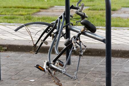 cadena rota: Bici encadenada a barandas con ambas ruedas desaparecidos
