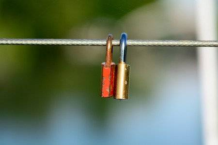 padlocks: Love padlocks swinging on bridge cable Stock Photo