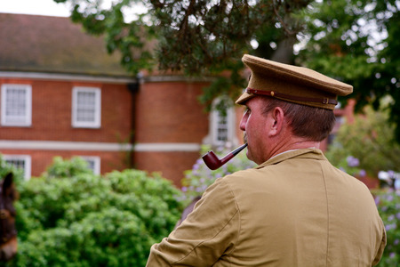 reenact: Bedford, England July 19, 2014: World War One re-enactment Cavalry soldier smoking pipe at Bedford River Festival