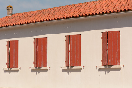 red shutters: Four red window shutters on French home Stock Photo