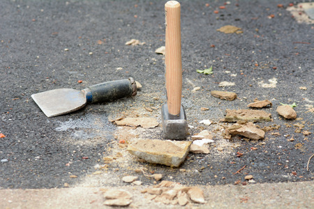 bolster: Bricklayers lump hammer and bolster chisel on ground