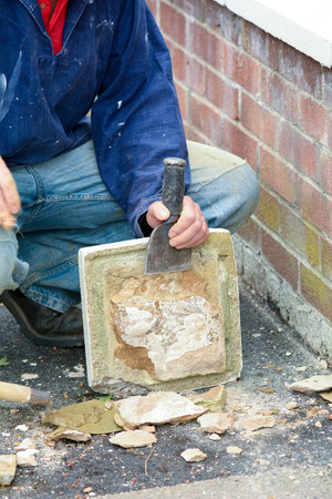 topper: Bricklayer using hammer and bolster to clear render off gate post topper