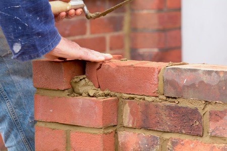 Bricklayer laying brick on wall Stock Photo