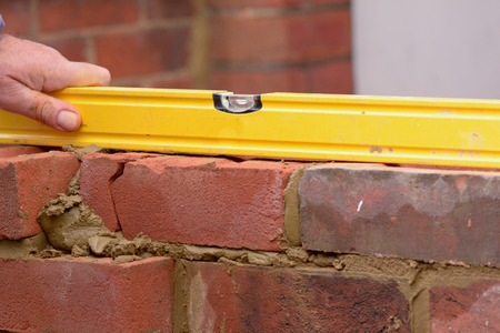 spirit level: Bricklayer using spirit level to check wall is horizontal