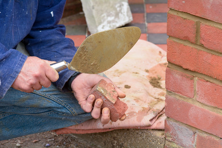 bricklayer: Bricklayer using trowel to clean render off old brick Stock Photo