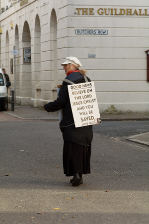 unsuspecting: Barnstaple, Devon, England on 21 October 2014: Woman with sandwich board promoting Christian faith in the town Editorial