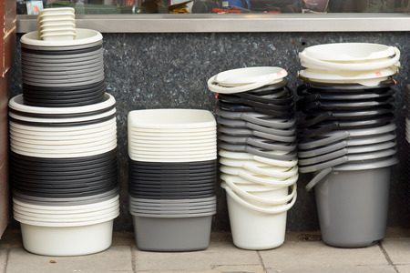 homeware: Stacks of plastic buckets and washing-up bowls outside shop Stock Photo