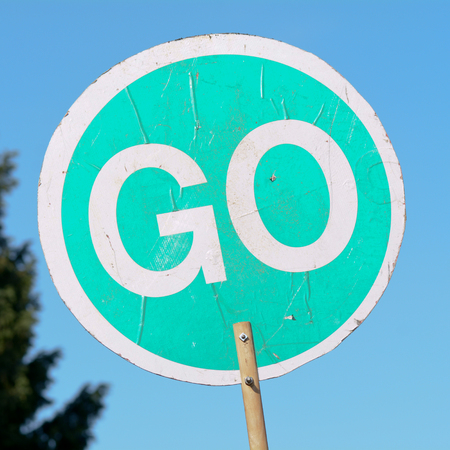 go sign: Go sign on stick used by construction workers to control traffic