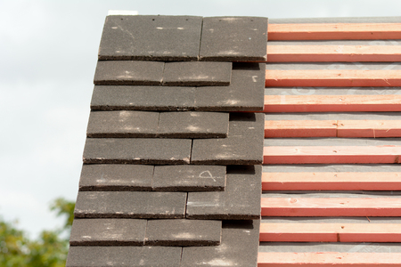 roof tiles: Roof tiles being fitted to wooden battens