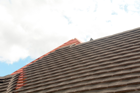 being: Roof tiles being fitted to wooden battens
