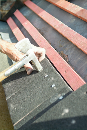 nailing: Man nailing roof tiles to wooden roof battens