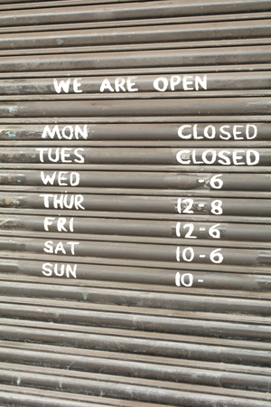 premises: Shop opening times painted on metal roller blinds