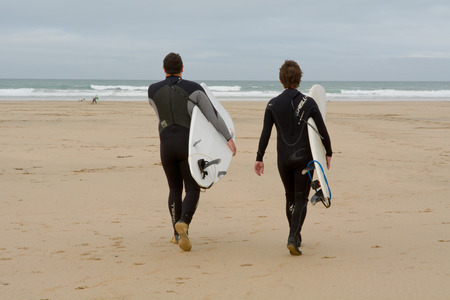 surfers: Perranporth, Cornwall, England October,23 2014: Two surfers with surfboards walking towards sea Editorial