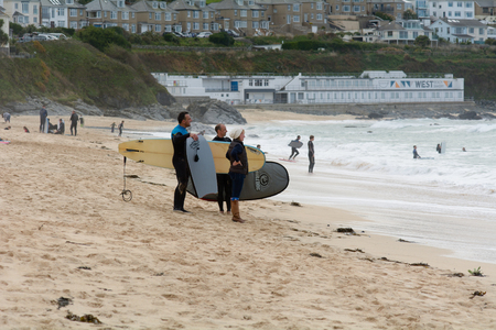 surfers: St Ives, Cornwall, England October,23 2014: Surfers on the beach Editorial