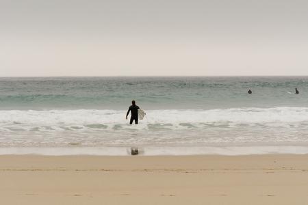 sennen: Sennen Cove, Cornwall, England October,24 2014: A surfer entering the sea Editorial