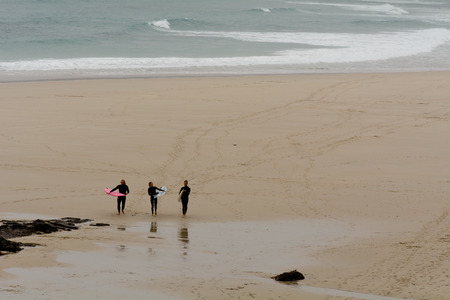 surfers: Sennen Cove, Cornwall, England October,24 2014: Three surfers leaving the beach after morning surfing