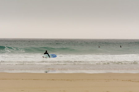 sennen: Sennen Cove, Cornwall, England October,24 2014: A surfer entering the sea with surfboard tucked under arm