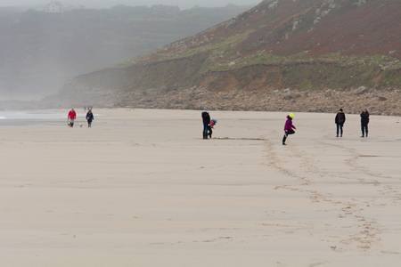 sennen: Sennen Cove, Cornwall, England October,24 2014: Children playing on the beach on cloudy wet day Editorial