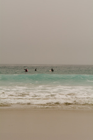 surfers: Sennen Cove, Cornwall, England October,24 2014: Surfers sat on boards waiting for the right wave