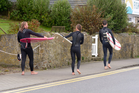 surfers: Sennen Cove, Cornwall, England October,24 2014: Three surfers heading home after morning surfing Editorial