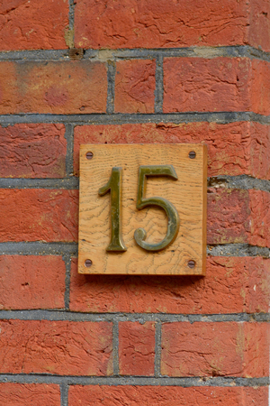 number 15: House number 15 sign on wall