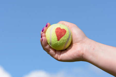 held: Tennis ball with love heart - held by woman player
