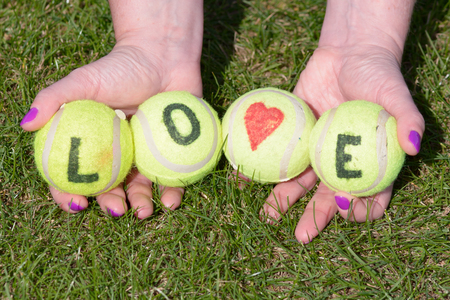 held: Tennis balls with love heart and word held by woman