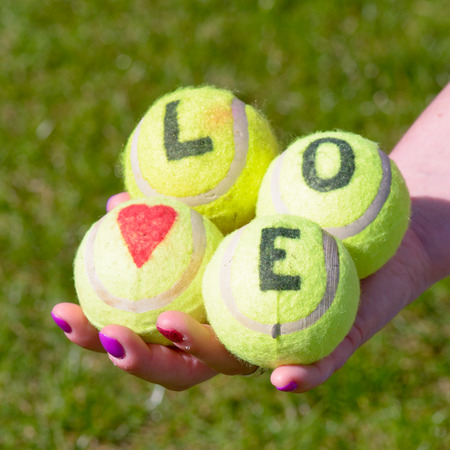 held down: Tennis balls with love heart and word held by woman