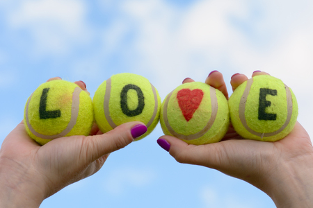 held: Tennis balls with love heart and word held aloft by woman