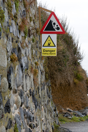 steep cliff sign: Danger Falling Objects sign next to cliff Stock Photo