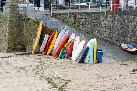 mousehole: Boats stacked against Mousehole harbour wall, Cornwall, England Stock Photo