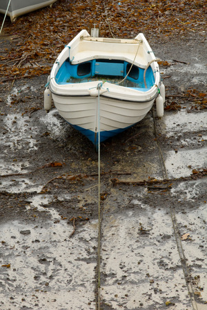 small white boat on sand at low tide in harbour