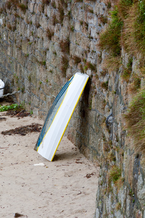 fibreglass: Small white boat leaning against harbour wall in Cornwall Stock Photo
